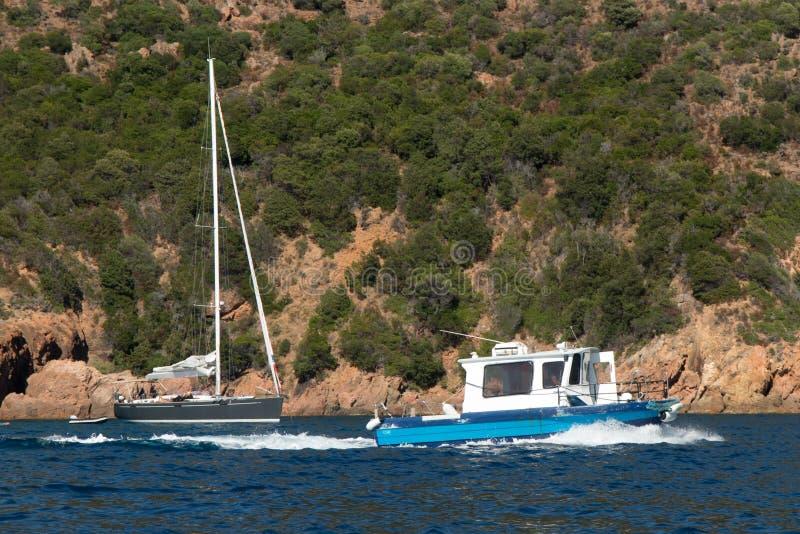 Πλέοντας βάρκα στην μπλε θάλασσα σε έναν κόλπο στην ακτή του νησιού της Κορσικής, Γαλλία στοκ εικόνες