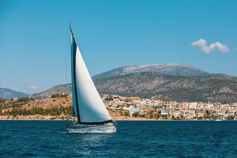 Πλέοντας ολισθήσεις βαρκών μέσω του νερού κατά μήκος της ακτής του ελληνικού νησιού στοκ εικόνα