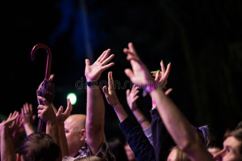 Πλήθος των ανθρώπων με τα χέρια τους επάνω κατά τη διάρκεια της συναυλίας βράχου στο σκοτεινό υπόβαθρο στοκ εικόνα με δικαίωμα ελεύθερης χρήσης