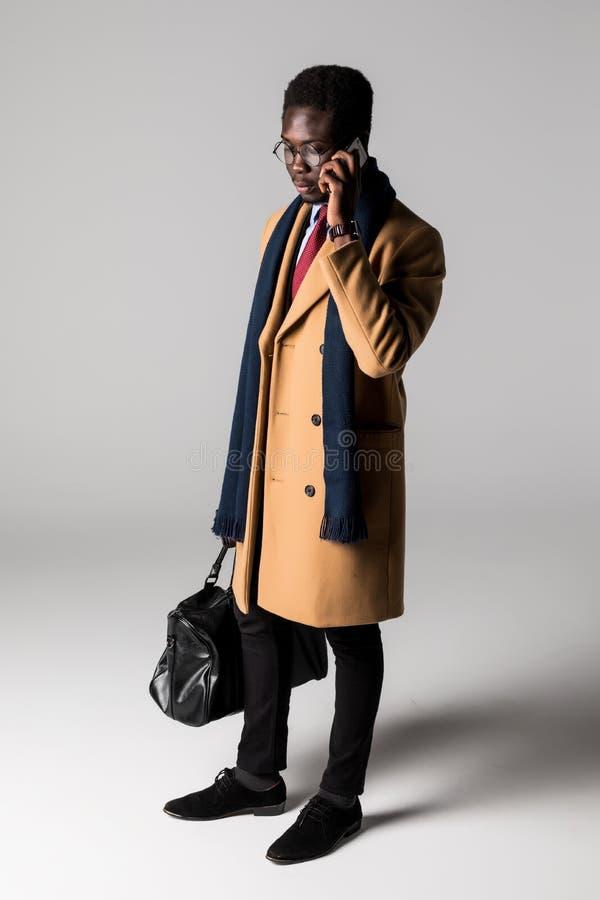Πλήρες δευτερεύον πορτρέτο μήκους του νέου αφρικανικού επιχειρηματία που χρησιμοποιεί το κινητό τηλέφωνο που απομονώνεται στοκ φωτογραφία με δικαίωμα ελεύθερης χρήσης