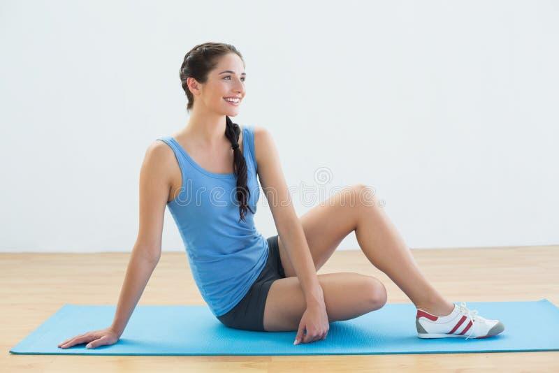 Πλήρες μήκος μιας συνεδρίασης γυναικών στο χαλί άσκησης στοκ φωτογραφία με δικαίωμα ελεύθερης χρήσης