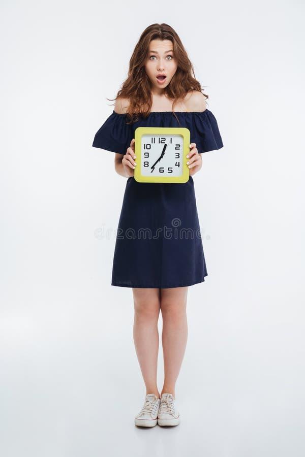 Πλήρες μήκος της έκπληκτης νέας γυναίκας που στέκεται και που κρατά το ρολόι στοκ εικόνες