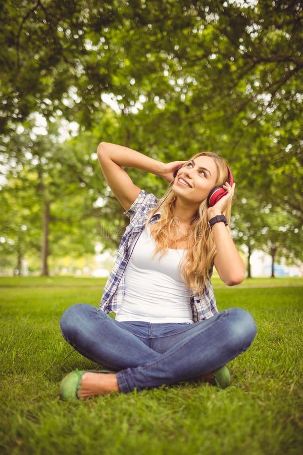 Πλήρες μήκος της ευτυχούς γυναίκας που απολαμβάνει τη μουσική στο πάρκο στοκ φωτογραφίες