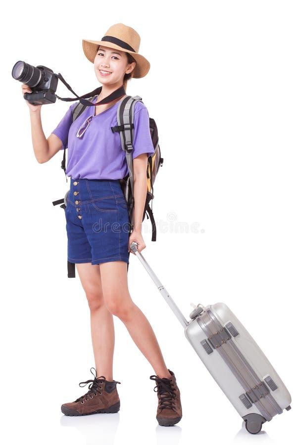 Πλήρες μήκος της νέας γυναίκας στο περιστασιακό περπάτημα με την τσάντα ταξιδιού στοκ εικόνα