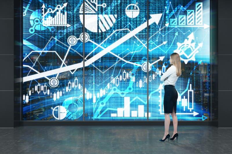 Πλήρες μήκος της νέας κυρίας που στέκεται μπροστά από την ψηφιακή οθόνη με τις γραφικές παραστάσεις, τα διαγράμματα και τα βέλη Μ στοκ εικόνες με δικαίωμα ελεύθερης χρήσης