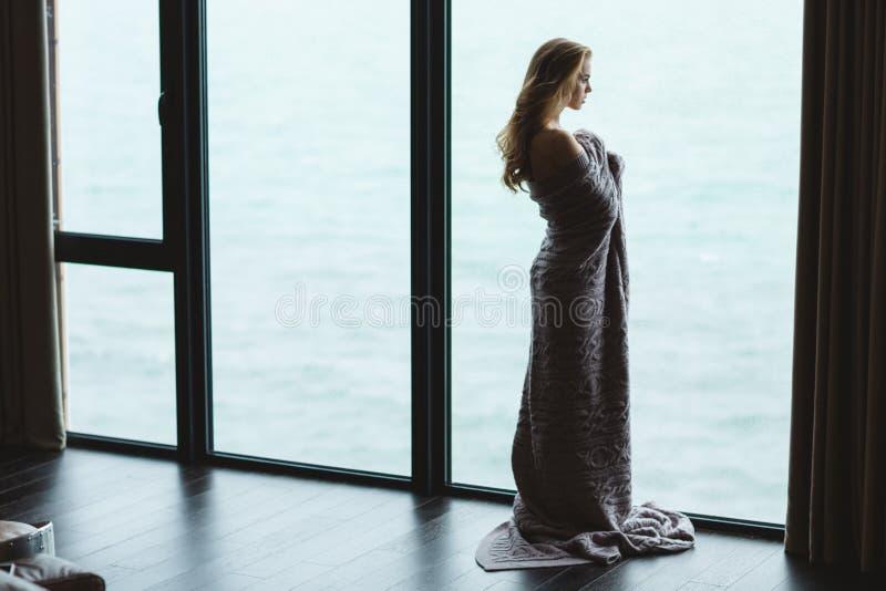 Πλήρες μήκος της σκεπτικής γυναίκας στο πλεκτό coverlet που απολαμβάνει τη θέα στοκ φωτογραφία