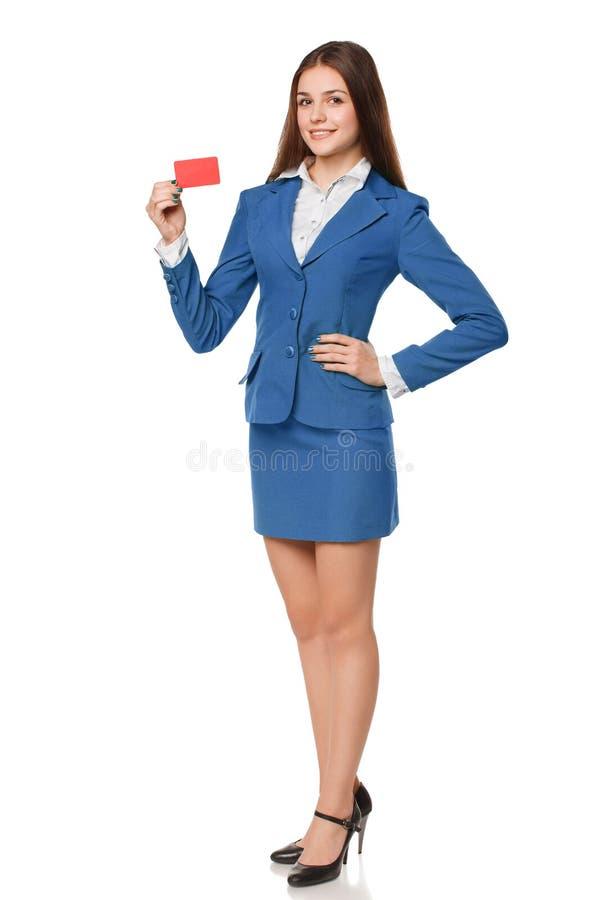 Πλήρες μήκος της χαμογελώντας επιχειρησιακής γυναίκας που παρουσιάζει κενή πιστωτική κάρτα κοστούμι, που απομονώνεται στο μπλε πέ στοκ εικόνες