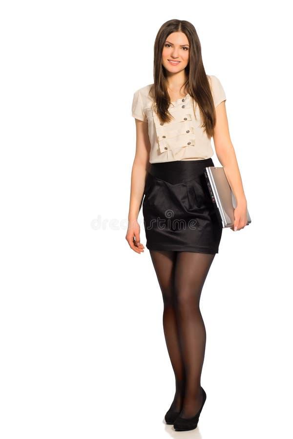 Πλήρες μήκος της χαμογελώντας όμορφης γυναίκας με το κλειστό lap-top στοκ εικόνα με δικαίωμα ελεύθερης χρήσης