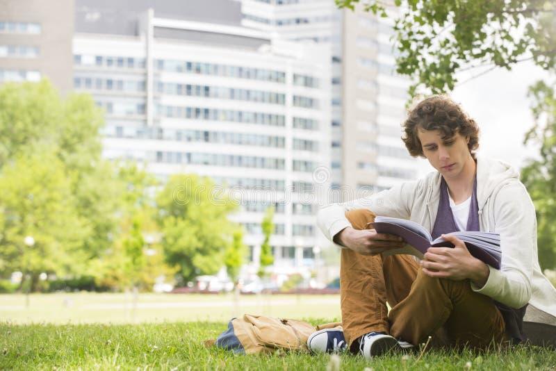 Πλήρες μήκος του βιβλίου ανάγνωσης νεαρών άνδρων στην πανεπιστημιούπολη κολλεγίων στοκ εικόνες