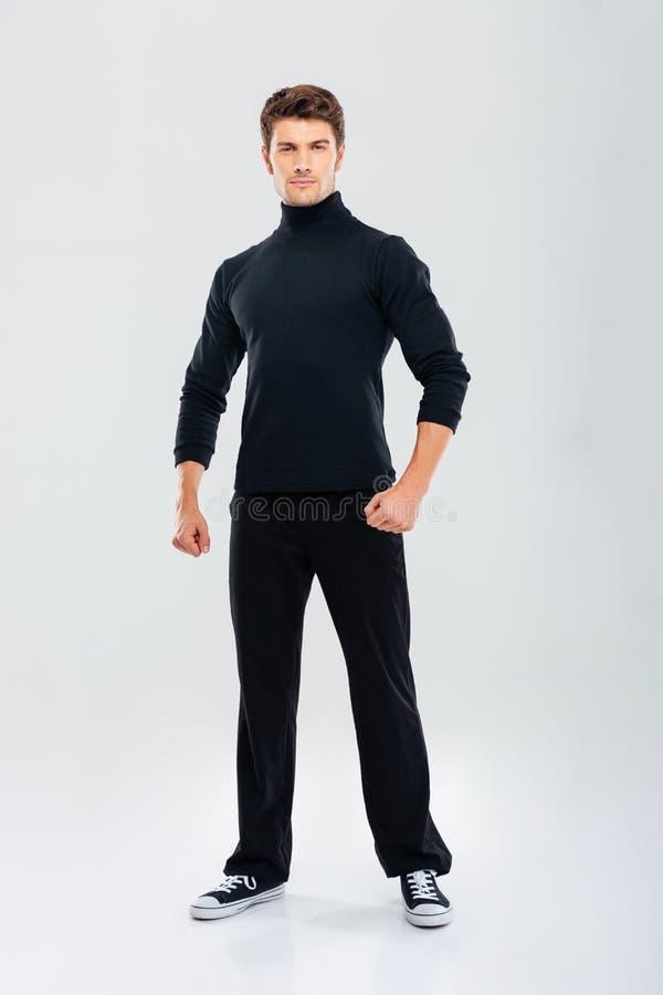 Πλήρες μήκος του ισχυρού νεαρού άνδρα στη μαύρη στάση ενδυμάτων στοκ φωτογραφίες με δικαίωμα ελεύθερης χρήσης