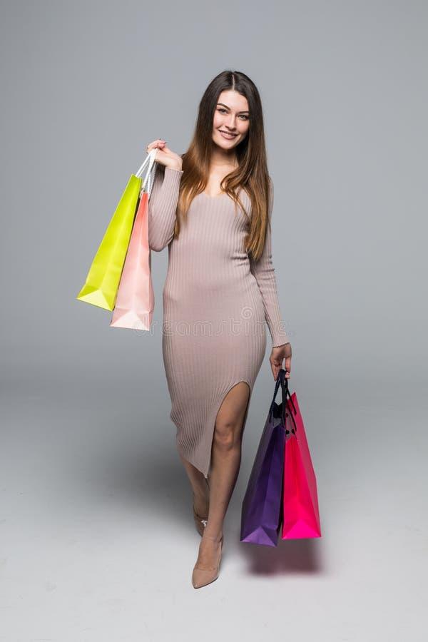 Πλήρες πορτρέτο μήκους μιας ευτυχούς συγκινημένης γυναίκας στο φόρεμα που στέκεται και που κρατά τις ζωηρόχρωμες τσάντες αγορών α στοκ φωτογραφίες με δικαίωμα ελεύθερης χρήσης