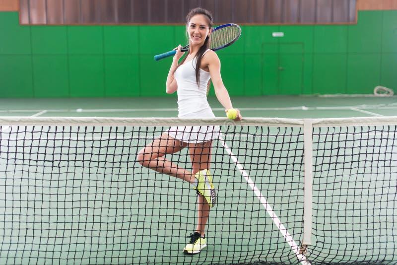 Πλήρες πορτρέτο μήκους μιας νέας παίζοντας αντισφαίρισης γυναικών στο δικαστήριο στοκ εικόνα