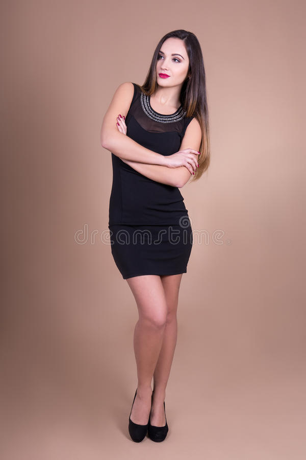 Πλήρες πορτρέτο μήκους της νέας όμορφης γυναίκας στο μαύρο φόρεμα ove στοκ φωτογραφία