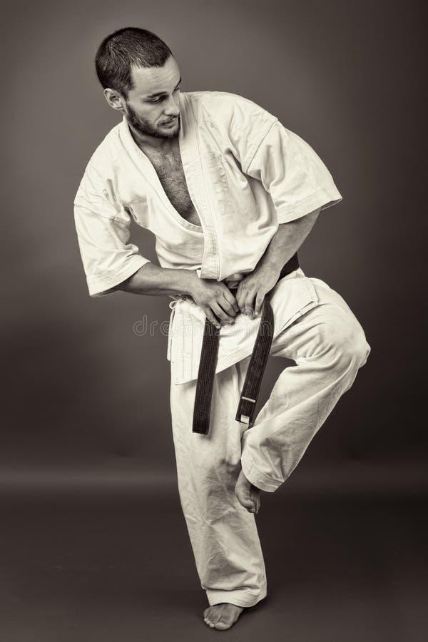 Πλήρες πορτρέτο μήκους του νεαρού άνδρα στο άσπρο κιμονό και τη μαύρη ζώνη στοκ εικόνες