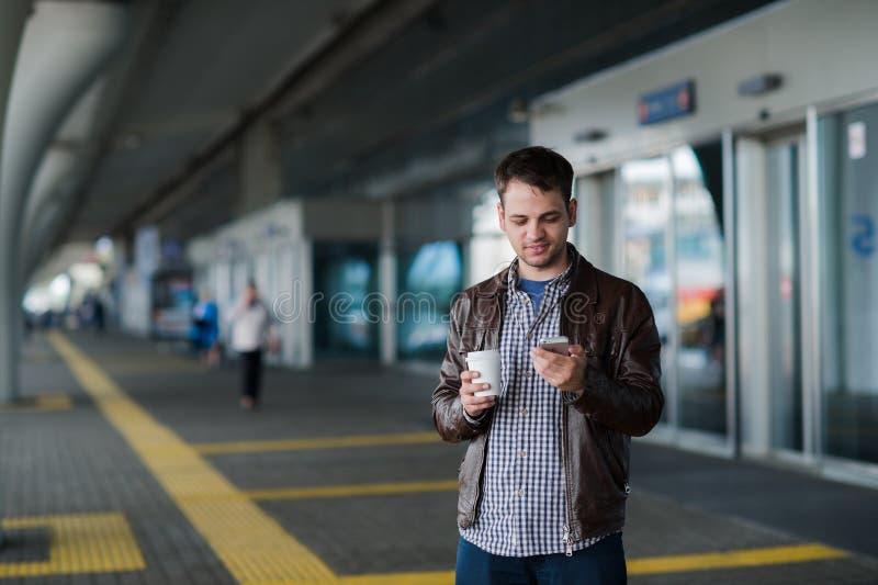 Πλήρες πορτρέτο σωμάτων ενός αρσενικού ταξιδιώτη που περπατά με το κινητό τηλέφωνο και τον καφέ στοκ φωτογραφία