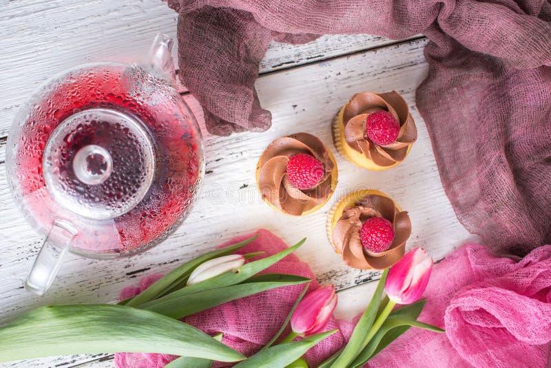 πλήρης άνοιξη λιβαδιών πικραλίδων ανασκόπησης κίτρινη Cupcakes και τσάι σε έναν πίνακα με τις ρόδινες τουλίπες Ακόμα ζωή με τη φρ στοκ εικόνες