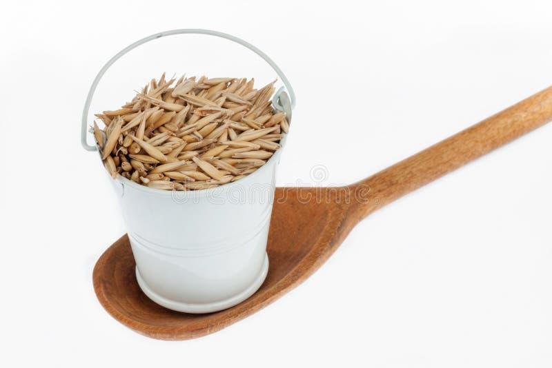 Πλήρης κάδος των στάσεων σιταριών βρωμών σε ένα ξύλινο κουτάλι στοκ φωτογραφία με δικαίωμα ελεύθερης χρήσης