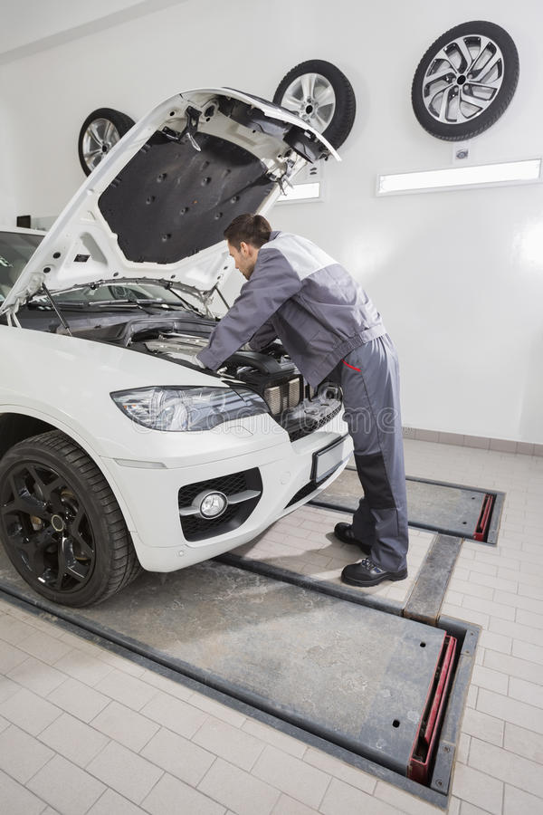 Πλήρης πλάγια όψη μήκους της αρσενικής αυτοκινητικής μηχανικής μηχανής αυτοκινήτων επισκευής στο κατάστημα επισκευής στοκ εικόνες