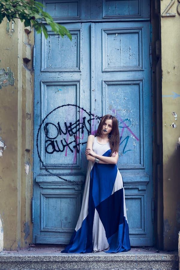 Πλήρης σύγχρονη γυναίκα πορτρέτου μόδας μήκους που στέκεται κοντά στην παλαιά πόρτα στοκ εικόνα με δικαίωμα ελεύθερης χρήσης