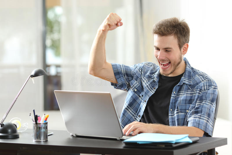 Πλήρους ευφορίας άτομο νικητών που χρησιμοποιεί ένα lap-top στο σπίτι στοκ εικόνα