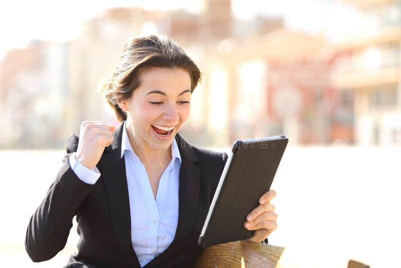 Πλήρους ευφορίας επιτυχής ανώτερος υπάλληλος που προσέχει μια ταμπλέτα στοκ φωτογραφία