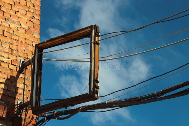 Πλαίσιο του παλαιού σπασμένου σημαδιού και των ηλεκτρικών καλωδίων σε μια γωνία στοκ φωτογραφία