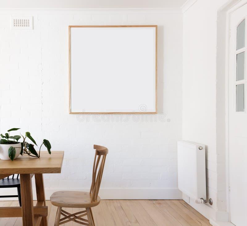 Πλαισιωμένη κενό τυπωμένη ύλη στον άσπρο τοίχο στο δανικό ορισμένο εσωτερικό dinin