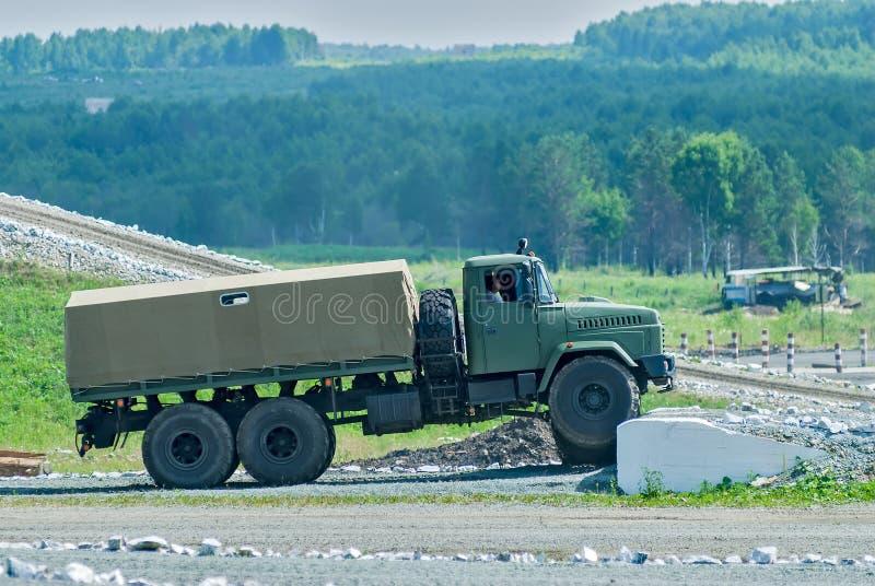 Πλαισιωμένο το κουρτίνα φορτηγό έρχεται γύρω στο υψηλό εμπόδιο στοκ φωτογραφία