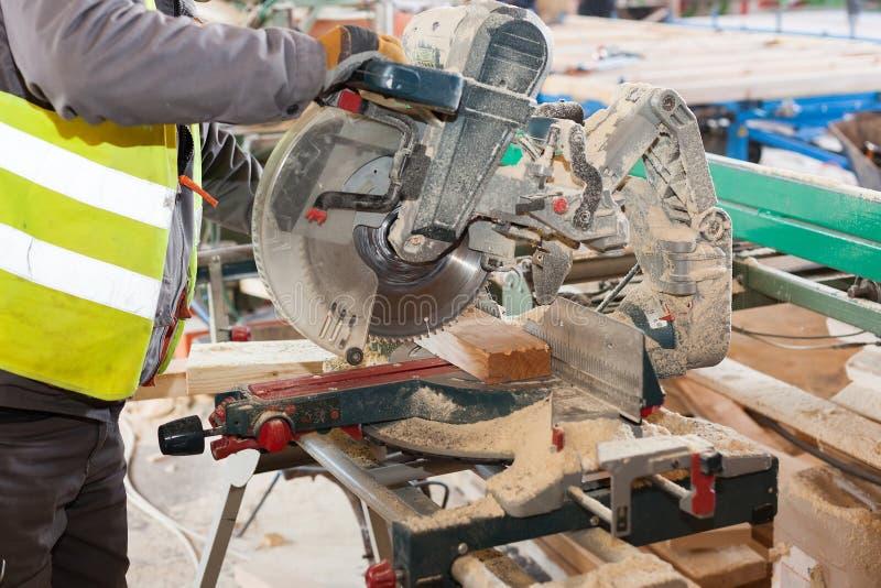 Πλαισιώνοντας ανάδοχος που χρησιμοποιεί ένα κομμένο εγκύκλιος πριόνι στα ξύλινα στηρίγματα περιποίησης στο μήκος στοκ εικόνες