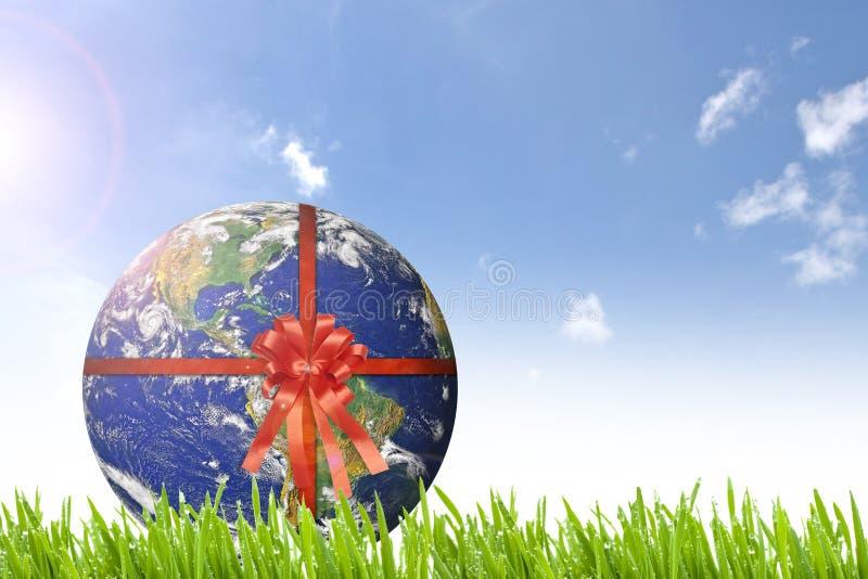 Πλανήτης Γη με την κόκκινη κορδέλλα στο όμορφο πράσινο ND ηλιόλουστο δ χλόης στοκ φωτογραφία με δικαίωμα ελεύθερης χρήσης