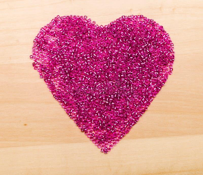 Πλαστικές χάντρες στην καρδιά που διαμορφώνεται στοκ φωτογραφία