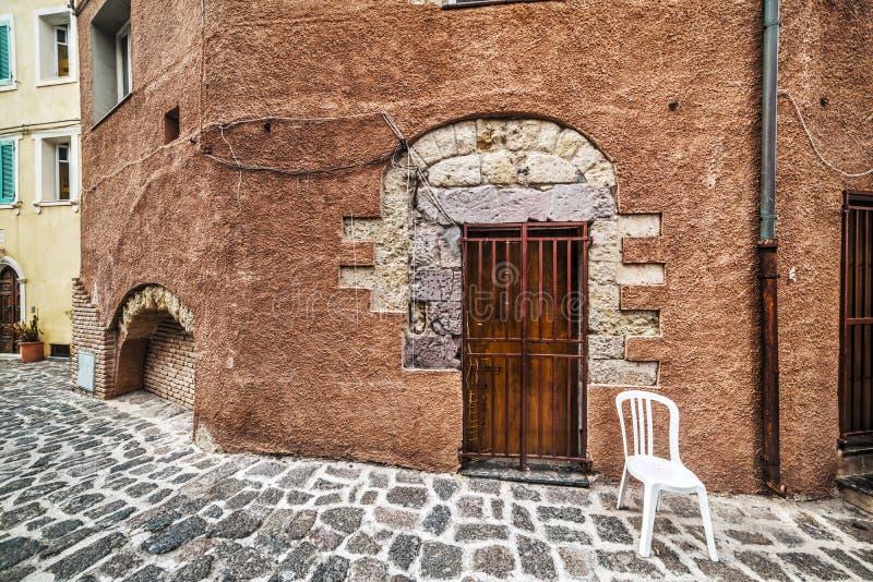 Πλαστική καρέκλα σε μια αγροτική γωνία σε Castelsardo στοκ εικόνα με δικαίωμα ελεύθερης χρήσης