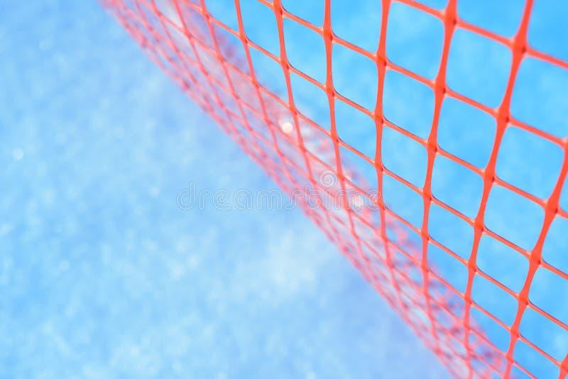 Πλαστικό δίχτυ ασφαλείας για το εργοτάξιο οικοδομής Πλέγμα κατασκευής στο χειμερινό χιόνι στοκ εικόνες
