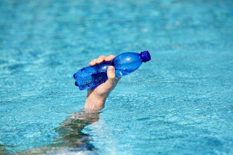 Πλαστικό μπουκάλι νερό εκμετάλλευσης χεριών στην επιφάνεια του νερού στοκ φωτογραφία