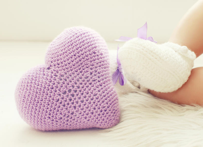 Πλεκτά καρδιά και μωρό ποδιών στα άσπρα bootees στοκ φωτογραφία με δικαίωμα ελεύθερης χρήσης