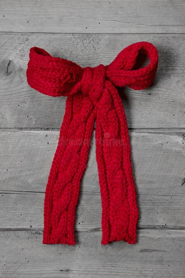Πλεκτό κόκκινο τόξο για ένα παρόν στο γκρίζο ξύλινο υπόβαθρο - greeti στοκ εικόνα με δικαίωμα ελεύθερης χρήσης