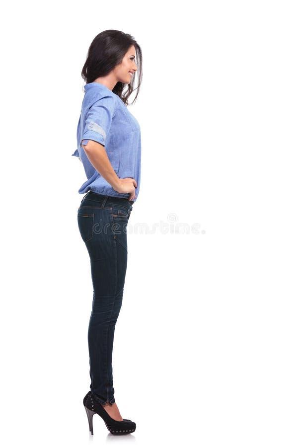 Πλευρά μιας περιστασιακής γυναίκας με τα χέρια στα ισχία στοκ φωτογραφίες