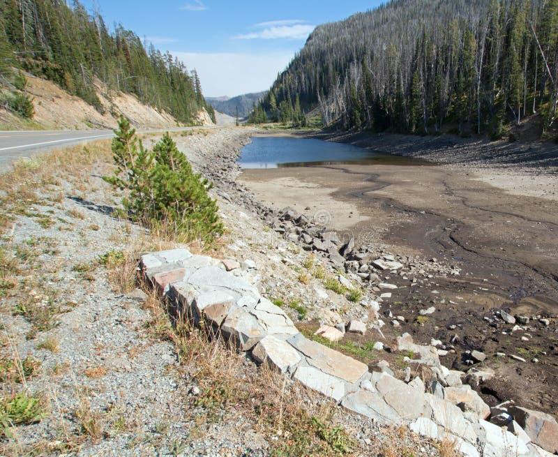 Πληγείσα από την ξηρασία λίμνη της Eleanor στο δασικό πέρασμα στην εθνική οδό στην ανατολική είσοδο του εθνικού πάρκου Yellowston στοκ φωτογραφίες