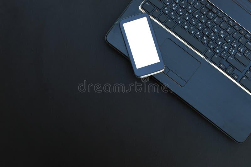 Πληκτρολόγιο και smartphone υπολογιστών σε ένα σκοτεινό υπόβαθρο Τοπ όψη στοκ εικόνες με δικαίωμα ελεύθερης χρήσης