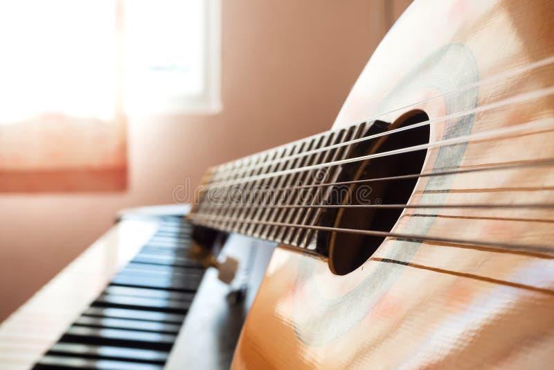 Πληκτρολόγιο πιάνων κινηματογραφήσεων σε πρώτο πλάνο με την κιθάρα στοκ φωτογραφίες