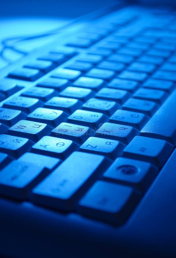 Πληκτρολόγιο υπολογιστών στο μπλε φως στοκ εικόνες