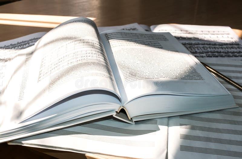 Πλημμυρισμένος με το φως: ανοικτό βιβλίο, μουσική φύλλων και σημειωματάριο μουσικής στοκ εικόνα