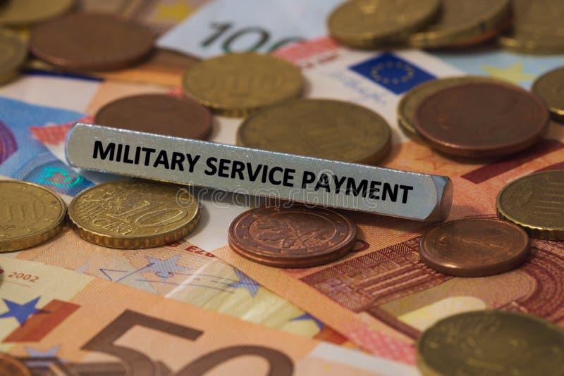 πληρωμή στρατιωτικής υπηρεσίας - η λέξη τυπώθηκε σε έναν φραγμό μετάλλων ο φραγμός μετάλλων τοποθετήθηκε σε διάφορα τραπεζογραμμά στοκ εικόνες με δικαίωμα ελεύθερης χρήσης