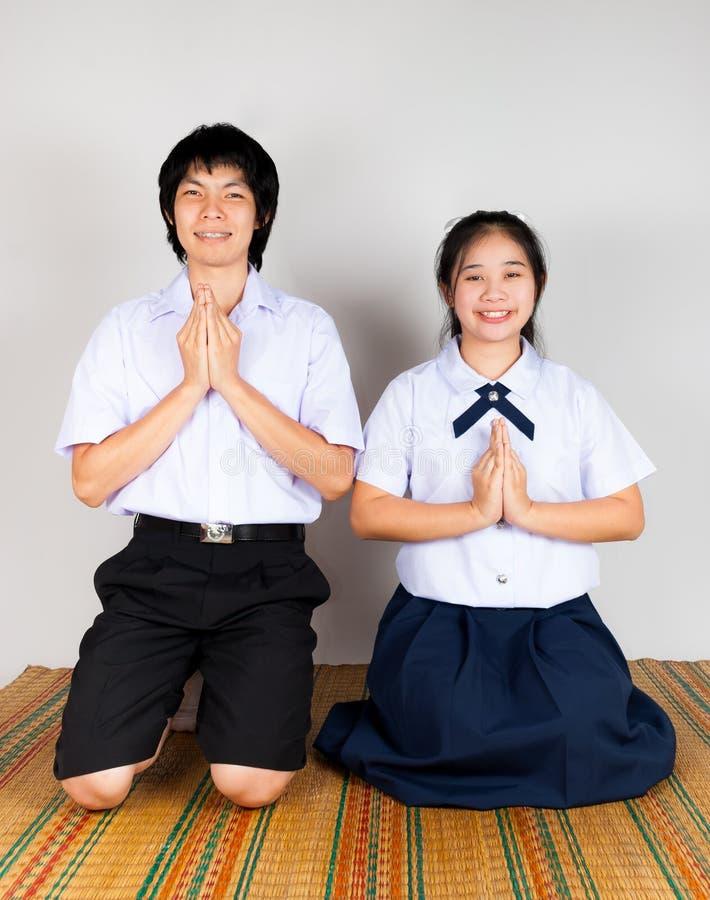 Πληρωμή της υπόκλισης των ασιατικών ταϊλανδικών σπουδαστών γυμνασίου στοκ εικόνες