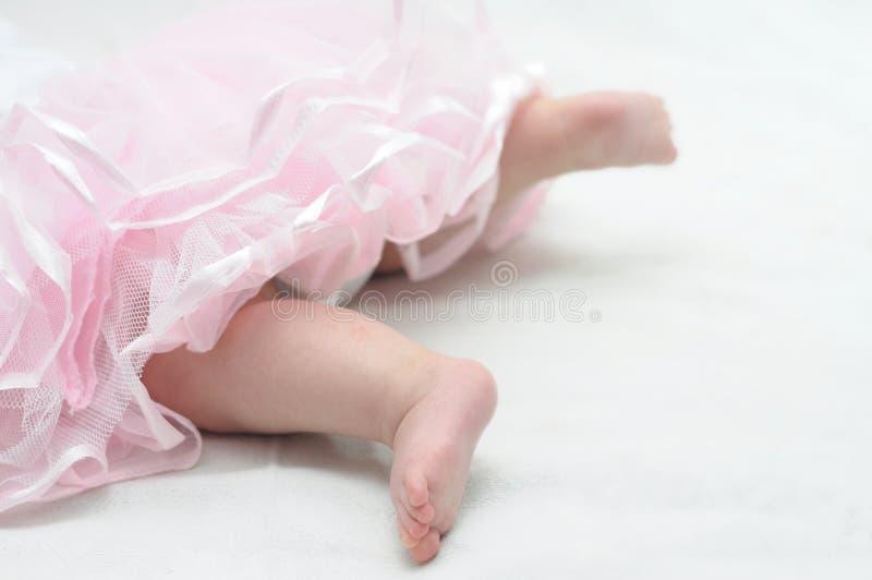 Πληρώνει του νεογέννητου μωρού στο ρόδινο χορό φορεμάτων στοκ φωτογραφία