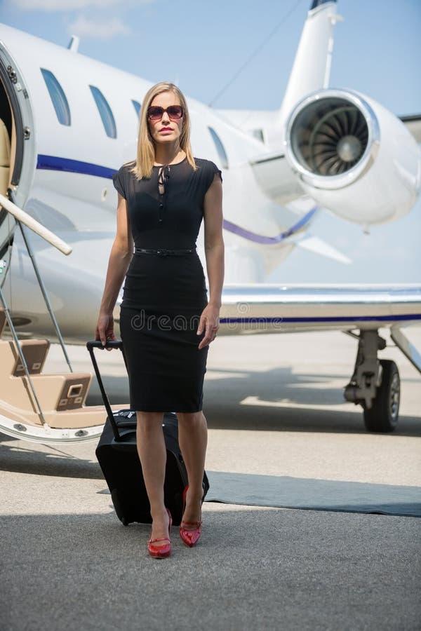 Πλούσια γυναίκα με τις αποσκευές που περπατά ενάντια σε ιδιωτικό στοκ εικόνες