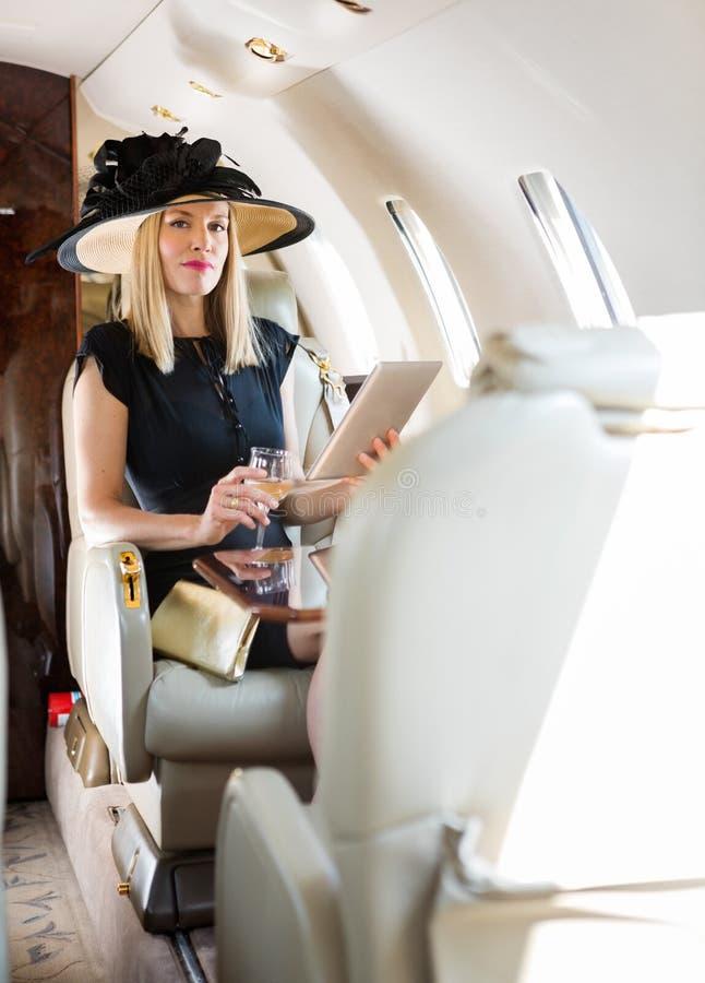 Πλούσια γυναίκα με το ποτό που χρησιμοποιεί την ψηφιακή ταμπλέτα μέσα στοκ φωτογραφία
