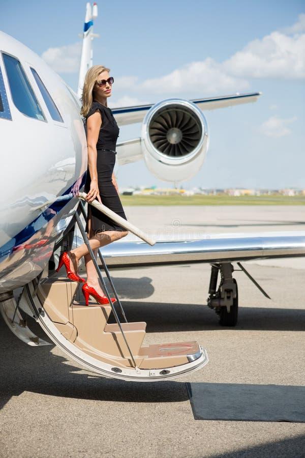 Πλούσια γυναίκα που αποβηβάζει το ιδιωτικό αεριωθούμενο αεροπλάνο στοκ εικόνα