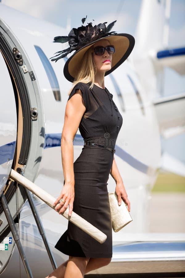 Πλούσια γυναίκα που παίρνει από το ιδιωτικό αεριωθούμενο αεροπλάνο στοκ φωτογραφία