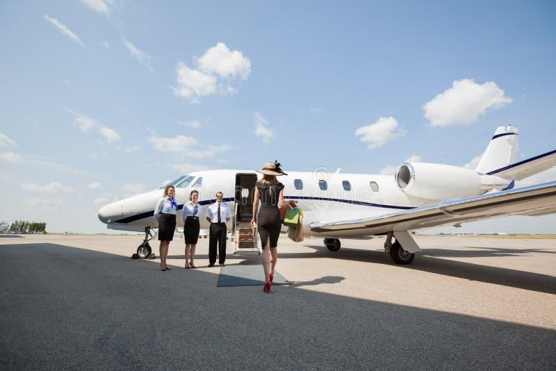 Πλούσια γυναίκα που περπατά προς το ιδιωτικό αεριωθούμενο αεροπλάνο στον αερολιμένα στοκ εικόνες